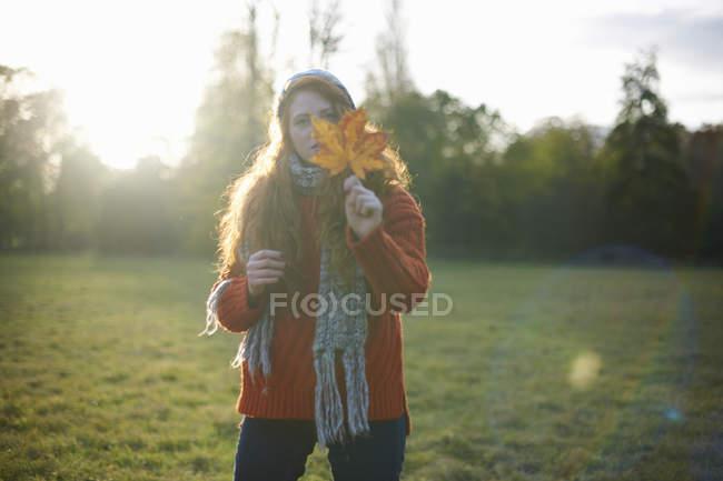 Женщина, держащая осенних листьев в сельской местности — стоковое фото