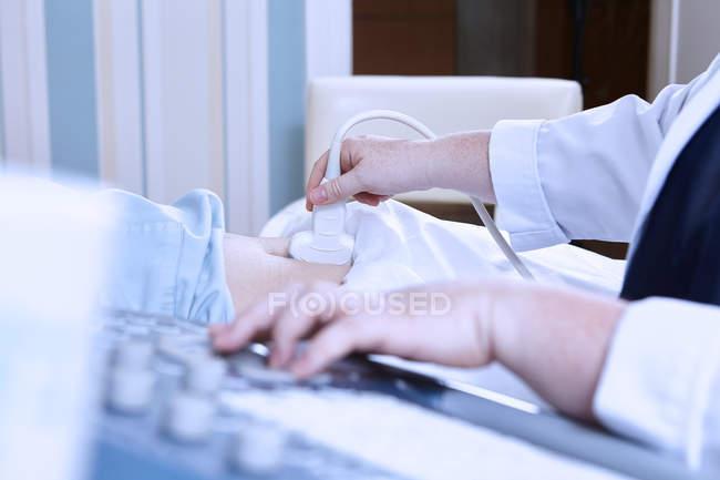 Ritagliate la vista di sonographer dando ultrasuono paziente incinta — Foto stock
