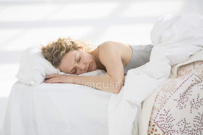 Женщина дома спит в белой кровати — стоковое фото