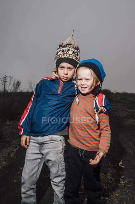 Портрет двух братьев в вязаных шляпах на открытом воздухе — стоковое фото