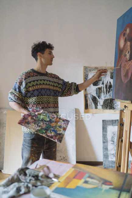 Male artist painting on canvas in studio — Stock Photo