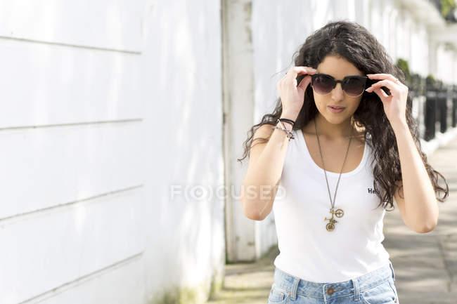 Junge Frau flaniert auf der Straße und setzt Sonnenbrille auf — Stockfoto
