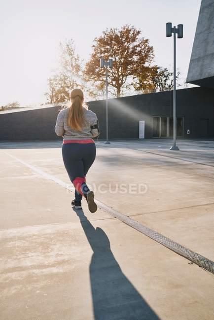 Vista trasera de la joven curvilínea corriendo - foto de stock