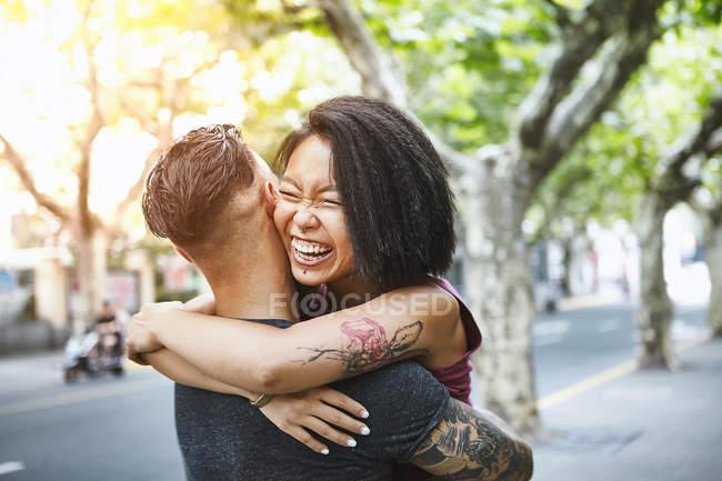 Pareja hipster multiétnica abrazándose en la calle, Shanghai French Concession, Shanghai, China - foto de stock