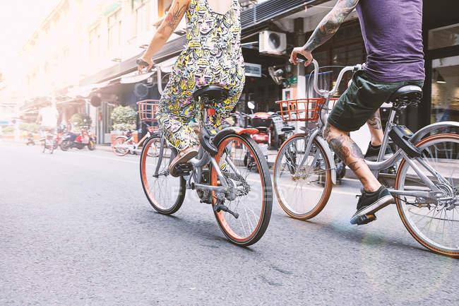 Vue de la taille vers le bas du couple hipster multi ethnique faisant du vélo le long de la rue, concession française de Shanghai, Shanghai, Chine — Photo de stock