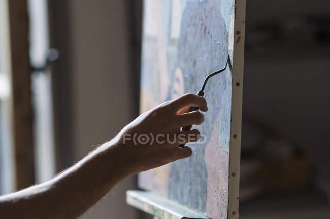 Чоловічий художник живопис на полотні у студії — стокове фото