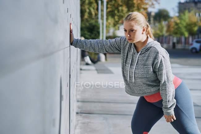 Изогнутая молодая женщина отжимается на стене — стоковое фото