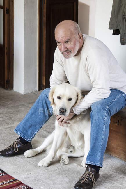 Portrait d'un homme senior à la maison avec chien — Photo de stock