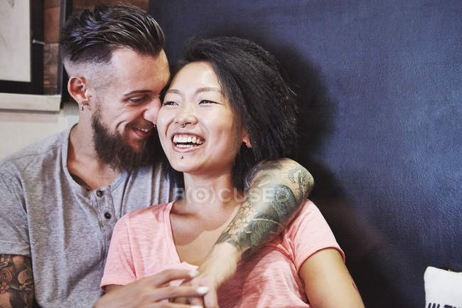 Multi ethnic hipster couple in cafe laughing, Shanghai French Concession, Shanghai, China — Stock Photo