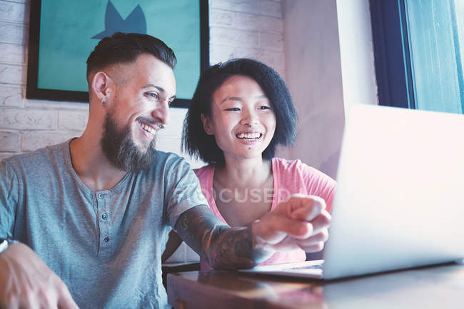 Multi ethnic hipster couple in cafe looking at laptop, Shanghai French Concession, Shanghai, China — Stock Photo