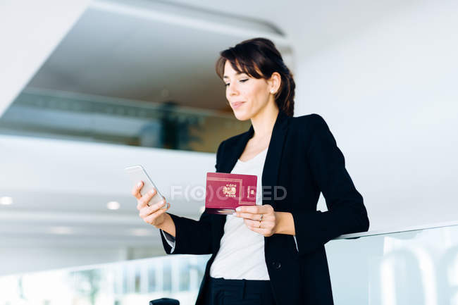 Businesswoman using mobile phone for electronic check-in — Stock Photo
