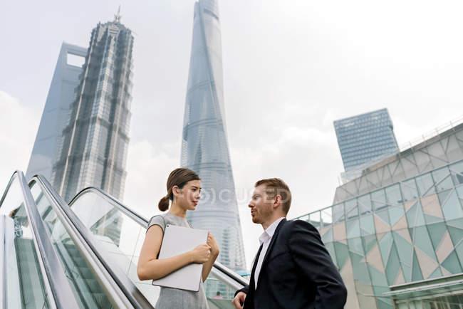 Jeune homme d'affaires et femme sur escalator dans la place financière de Shanghai, Chine — Photo de stock