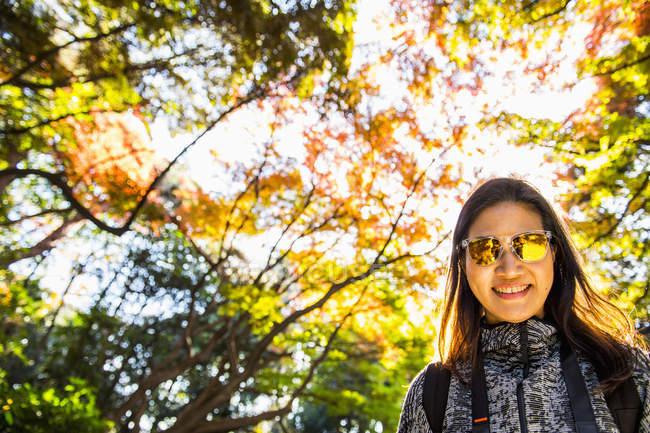 Faible angle vue de femme asiatique avec des lunettes de soleil jaunes au jardin National Shinjuku Gyoen, Tokyo — Photo de stock