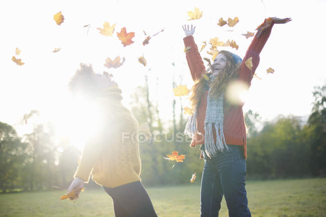 Female friends throwing autumn leaves in air — Stock Photo