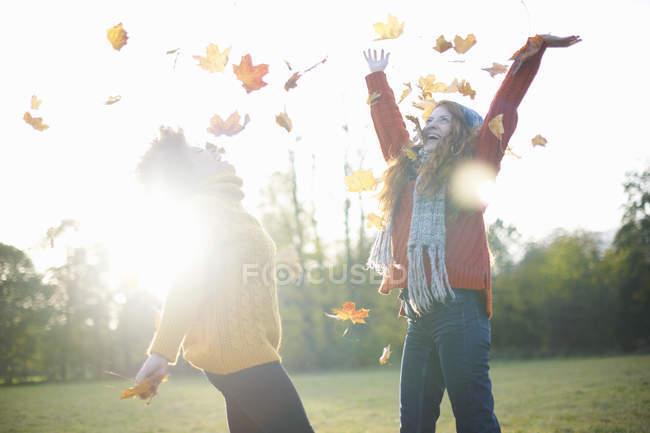 Amigos femininos jogando folhas de outono no ar — Fotografia de Stock
