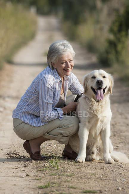 Porträt einer Seniorin, die neben Hund hockt — Stockfoto