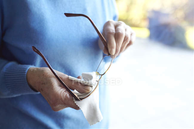 Senior woman cleaning eyeglasses with cloth, mid section — Stock Photo