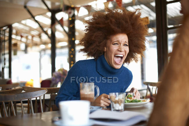 Женщина смеется во время ужина в кафе с другом — стоковое фото