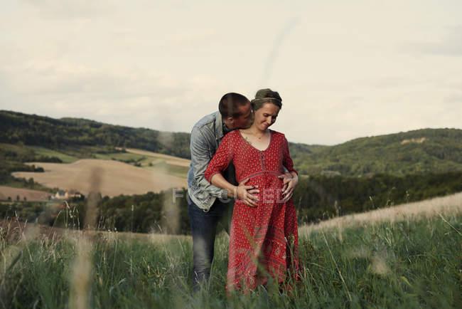 Романтичный мужчина с руками на животе беременной жены в поле — стоковое фото