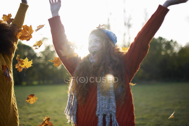 Two young women throwing autumn leaves in air — Stock Photo