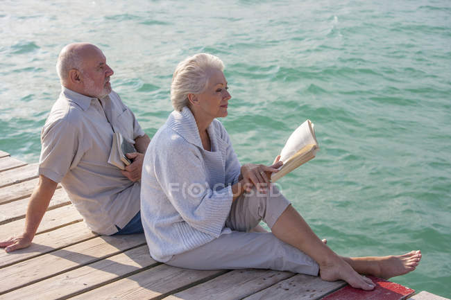 Senior couple enjoying seaside from jetty — Stock Photo