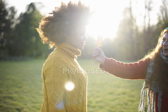 Woman holding leaf in front of friend — Stock Photo