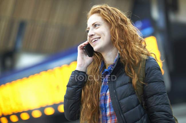 Mujer joven hablando en el teléfono inteligente en la estación de tren - foto de stock