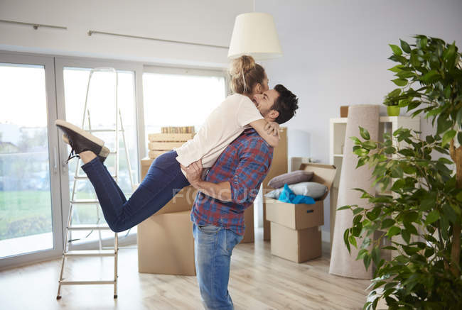 Young couple hugging at new home — Stock Photo