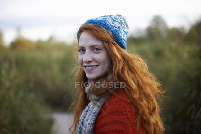 Ritratto di donna dai capelli rossi che guarda oltre la spalla la macchina fotografica — Foto stock