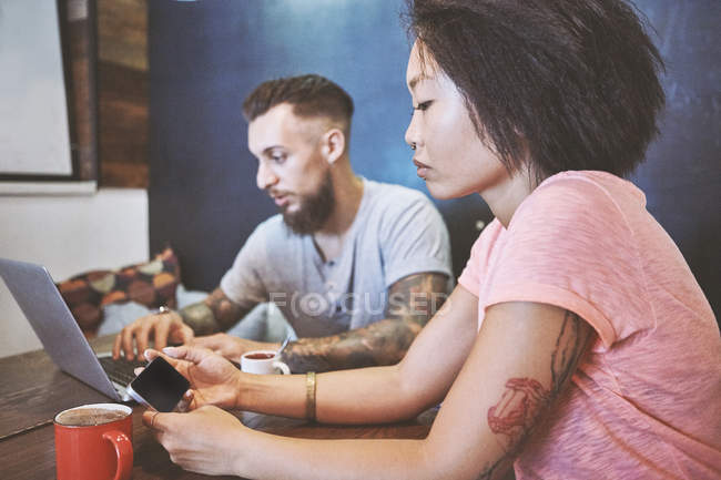 Multi ethnic hipster couple in cafe looking at smartphone and laptop, Shanghai French Concession, Shanghai, China — Stock Photo