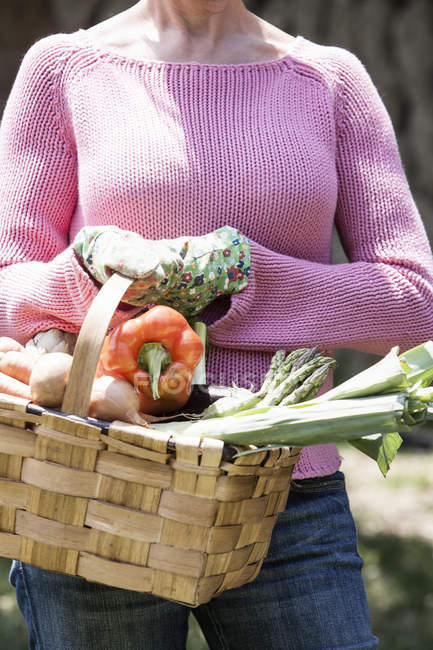 Woman with basket of homegrown vegetables — Stock Photo