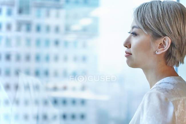 Портрет деловой женщины, выглядывающей в окно — стоковое фото