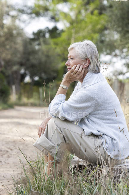 Senior woman sitting in rural setting, thoughtful expression — Stock Photo