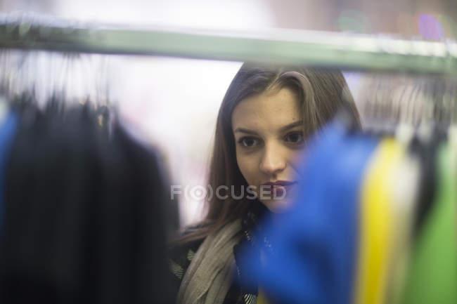 Jeune femme choisir des vêtements dans la boutique — Photo de stock