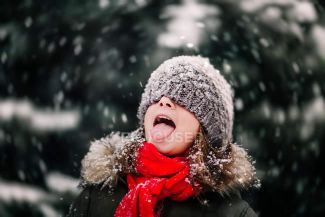 Портрет девушки ловить падающий снег на язык — стоковое фото