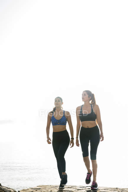 Two young women training and walking on beach — Stock Photo