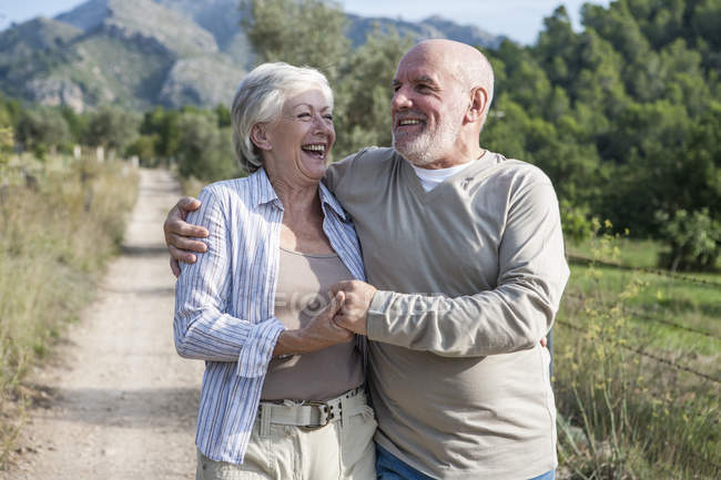 Senior couple walking together in rural setting, holding hands, smiling — Stock Photo