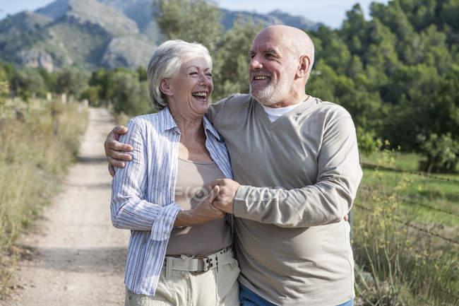 Senioren gehen zusammen in ländlicher Umgebung, halten Händchen, lächeln — Stockfoto