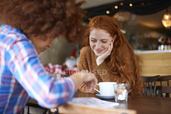 Two female friends relaxing in cafe — Stock Photo