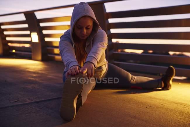 Curvilínea mujer joven entrenando y tocando dedos de los pies en pasarela - foto de stock
