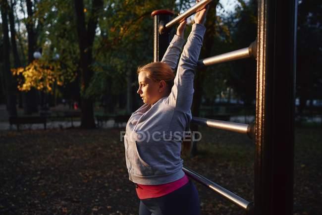 Изысканная молодая женщина, захватывающая тренажерный бар в парке — стоковое фото