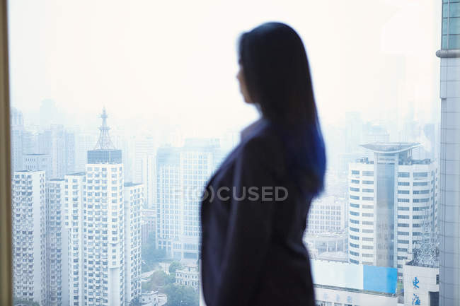 Side view of businesswoman looking through window at cityscape — Stock Photo