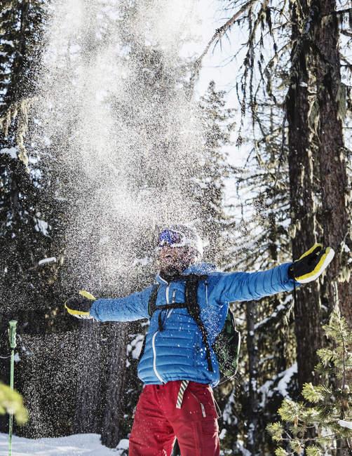 Porträt eines männlichen Skifahrers, der Schnee in die Luft wirft — Stockfoto