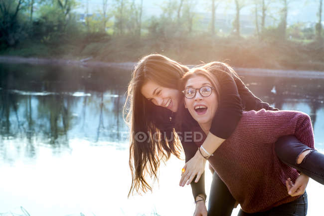 Young woman giving best friend on piggy back by river — Stock Photo