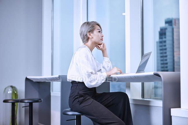 Бизнесмен, использующая ноутбук в современном офисе — стоковое фото