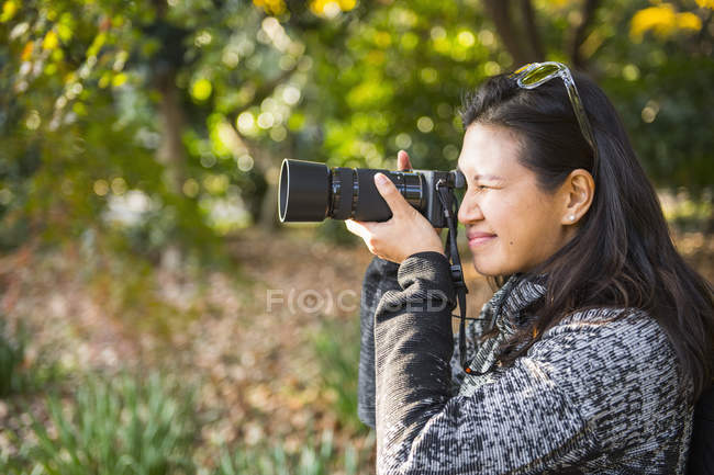 Side view of Woman taking pictures with digital camera, Shinjuku Gyoen National Garden, Tokyo — Stock Photo