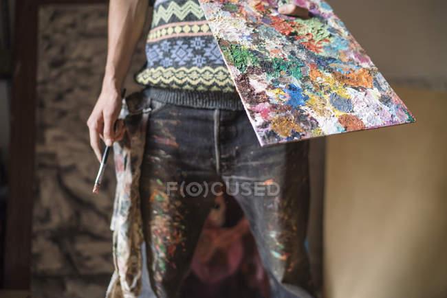 Артист тримає палітри і фарб пензля в студії — стокове фото