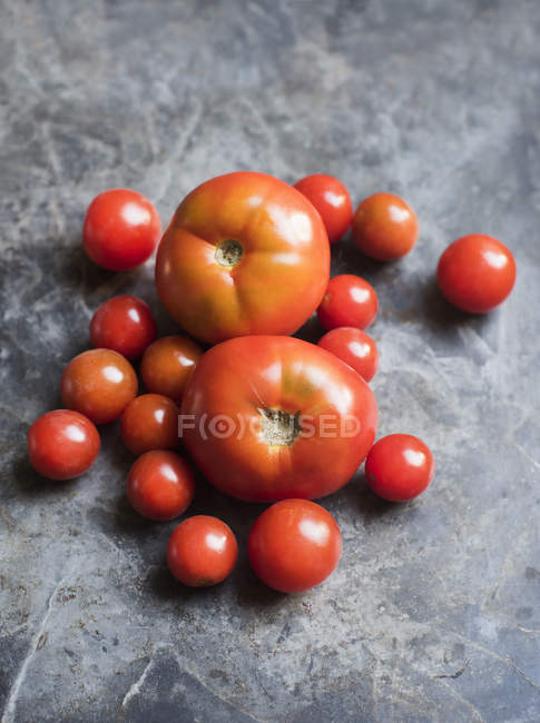 Ripe fresh tomatoes on grey tabletop — Stock Photo