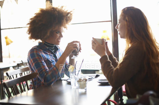 Two young female talking in coffee shop — Stock Photo