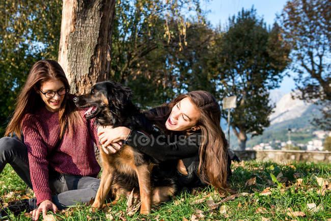 Two young women hugging dog — Stock Photo
